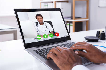 Close-up Of A Person Video Conferencing With Female Doctor Through Laptop