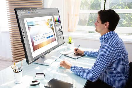 Jeune éditeur masculin à l'aide de tablette graphique pour croquis tout en travaillant sur ordinateur Banque d'images