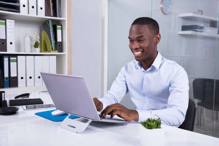 Portrait Of Smiling Young Businessman Using Laptop At Workplace Standard-Bild