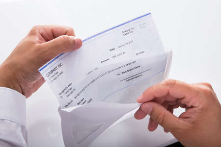 Close-up of a businessman's hand opening envelope with paycheck Standard-Bild - 105800814