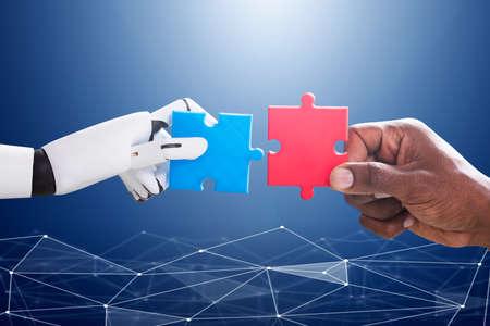 Roboter und menschliche Hand, die rote und blaue Stichsäge über dem blauen digitalen Hintergrund verbinden