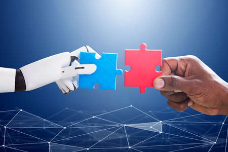 Robot And Human Hand Joining Red And Blue Jigsaw Over The Blue Digital Background