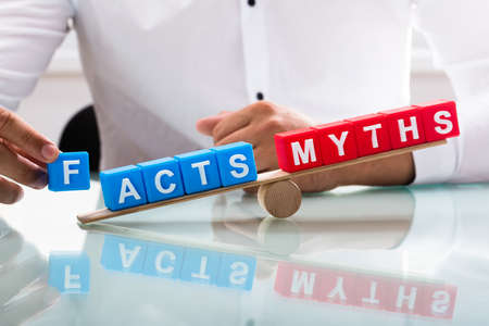 Businessman's hand showing unbalance between facts and myths on wooden seesaw