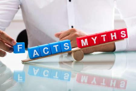 Zakenman hand met onbalans tussen feiten en mythen op houten wip