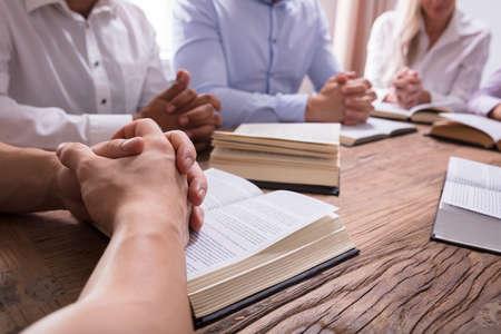 Nahaufnahme eines Mannes, der Hand auf Bibel über hölzernem Schreibtisch betet Standard-Bild