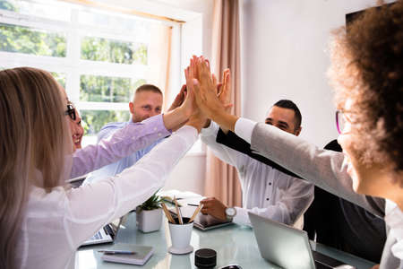 Group Of Businesspeople Giving High Five Over Desk At Workplace