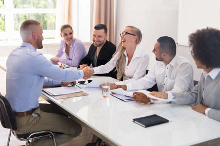 Smiling Young Man Shaking Hands With Female At Interview Stock Photo