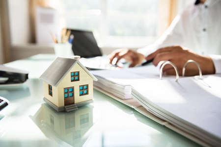 Businessman's hand calculating invoice with house model in office