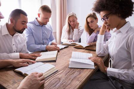 Grupa Młodych Ludzi Wieloetnicznych Czytania Biblii Na Drewnianym Biurku