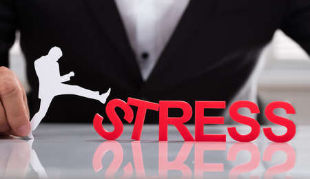Businessperson holding human figure kicking red stress word on reflective desk Stock Photo