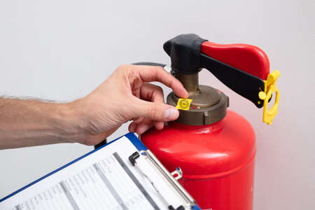 Young Male Technician Checking Symbol On Fire Extinguisher