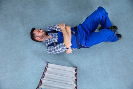 Injured Handyman Lying On Floor After Falling From Ladder