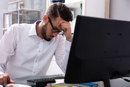 Stressed Young Businessman Sitting Near Computer In Office Stock Photo