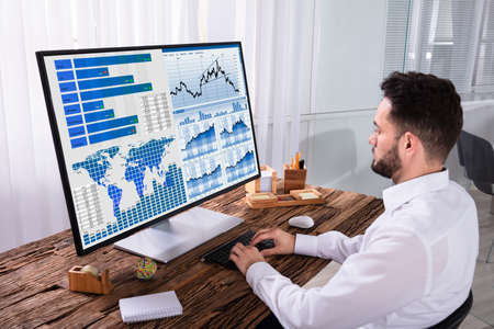 Young Male Stock Market Broker Analyzing Graph On Computer In Office