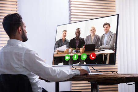 Young Businessman Video Conferencing With His Partner On Computer At Workplace Stock Photo