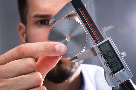 Close-up Of A Mans Hand Measuring Gears Size With Digital Electronic Vernier Caliper