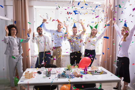 Excited Businesspeople Having Fun Raising Their Arms Among Party Confetti