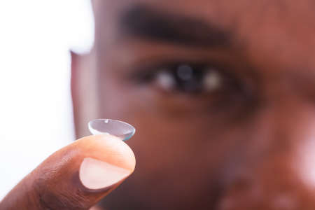Close-up Of A Man Holding Transparent Contact Lens In His Finger