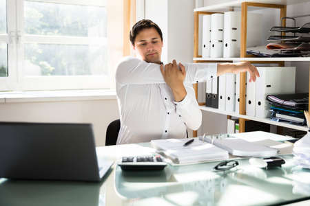 Young businessman stretching his arms at workplace