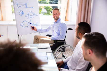 Disabled Young Businessman Giving Presentation To His Colleague Фото со стока