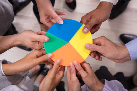 Elevated View Of Businesspeople Holding Multi Colored Pie Chart Фото со стока