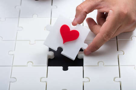 Persons hand placing last piece with red heart into white jigsaw puzzle Фото со стока