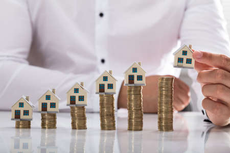 Businessmans hand placing house model on increasing golden stacked coins
