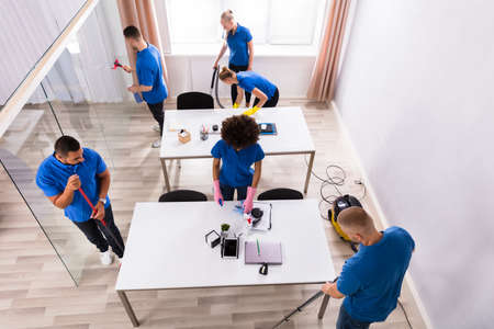 High Angle View Of Janitors In Uniform Cleaning Modern Office