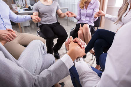 Group Of People Sitting In Circle Holding Hands