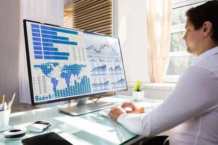 Junger männlicher Börsenmakler, der Grafik auf Computer am Arbeitsplatz analysiert