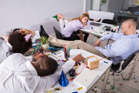 Group Of Businesspeople Sleeping In Office After New Year Party Фото со стока