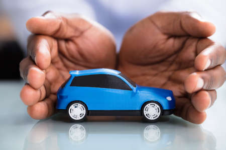 Businessmans Hand Protecting Blue Toy Car On The Reflective Desk