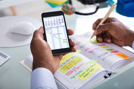 Businessman Holding Cellphone With Gantt App And Calendar Writing Schedule In Diary With Pen