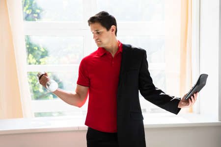Young businessman picking up calculator and dumbbell simultaneously in office