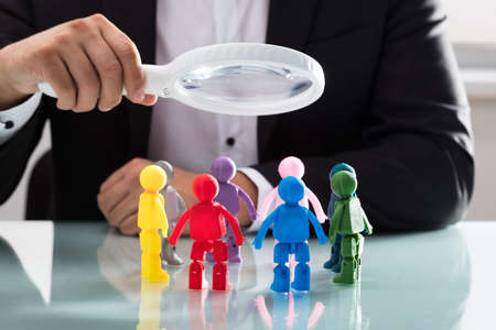 Businesspersons hand holding magnifying glass over multi colored human figures on reflective desk
