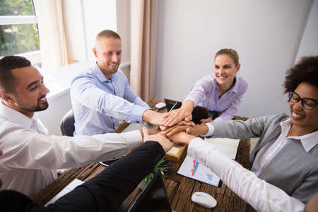 Group Of Smiling Young Businesspeople Stacking Hands In Office