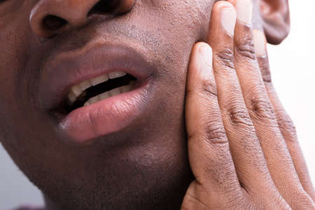 Close-up Of A Man Having Toothache Against White Background Фото со стока