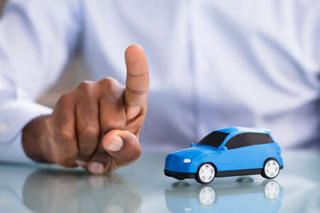 Close-up Of A Businessman Pointing Finger With Blue Toy Car On The Desk