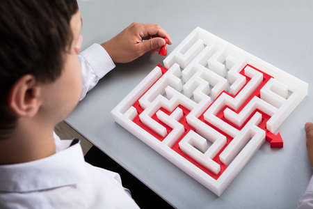 Elevated view of businessman solving maze on desk