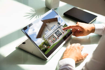 Close-up of businessmans hand checking house on laptop
