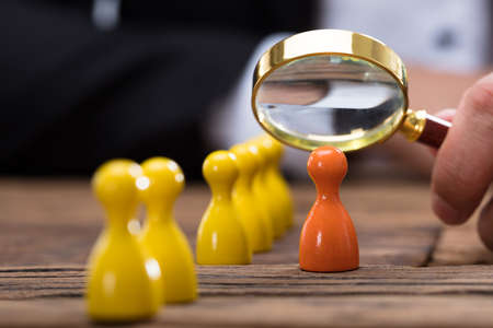 Businesspersons hand holding magnifying glass over orange pawn on wooden desk Фото со стока