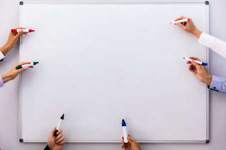 Businesspeople Writing On Blank White Board With Markers