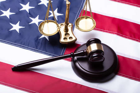 Elevated View Of Gavel And Golden Justice Scale On American Flag Фото со стока