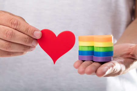 Close-up of a mans hand holding gay pride hearts