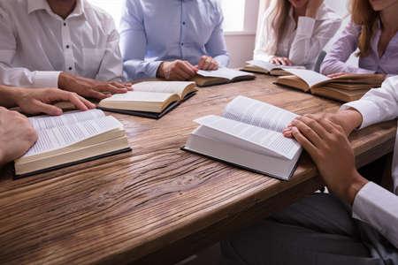 Grupo de personas leyendo la Biblia en un mostrador de madera