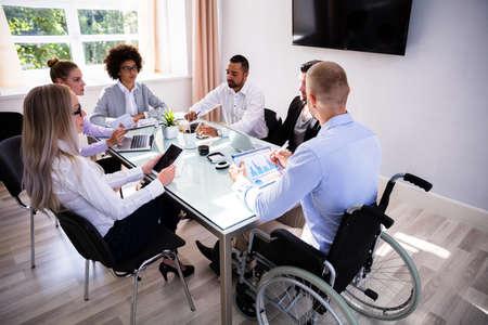 Manager Maschio Disabile Seduto Con I Suoi Colleghi Sul Posto Di Lavoro Archivio Fotografico