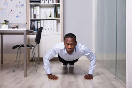 Young African American Man Doing Pushup In Front Of Closed Glass Door