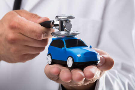Close-up of a doctors hand examining blue car