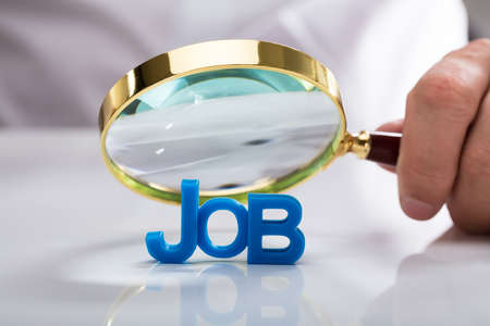 Businessmans hand holding magnifying glass over blue job word