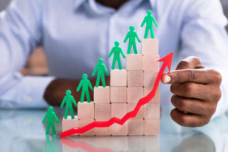 Businessman Pointing At Increasing Red Arrow In Front Of Wooden Blocks With Green Figures